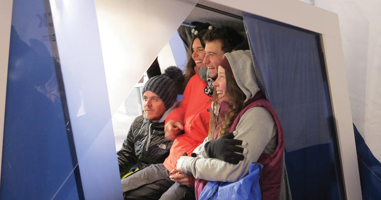 Four people together inside video booth recording a message
