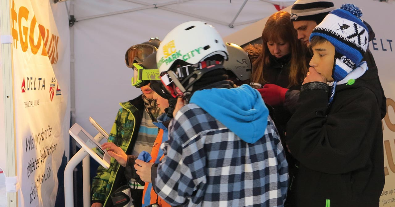Group of young skiiers/snowboarders share their videos from iPad stands.