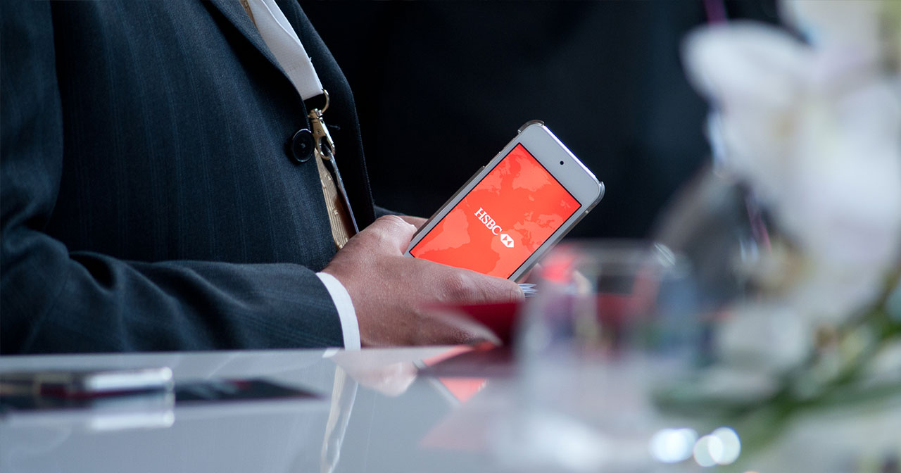 Man in a suit holding an iPod with HSBC logo on the screen