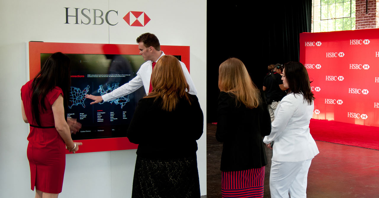 Man gestures/touches a large touchscreen while 4 people observe.