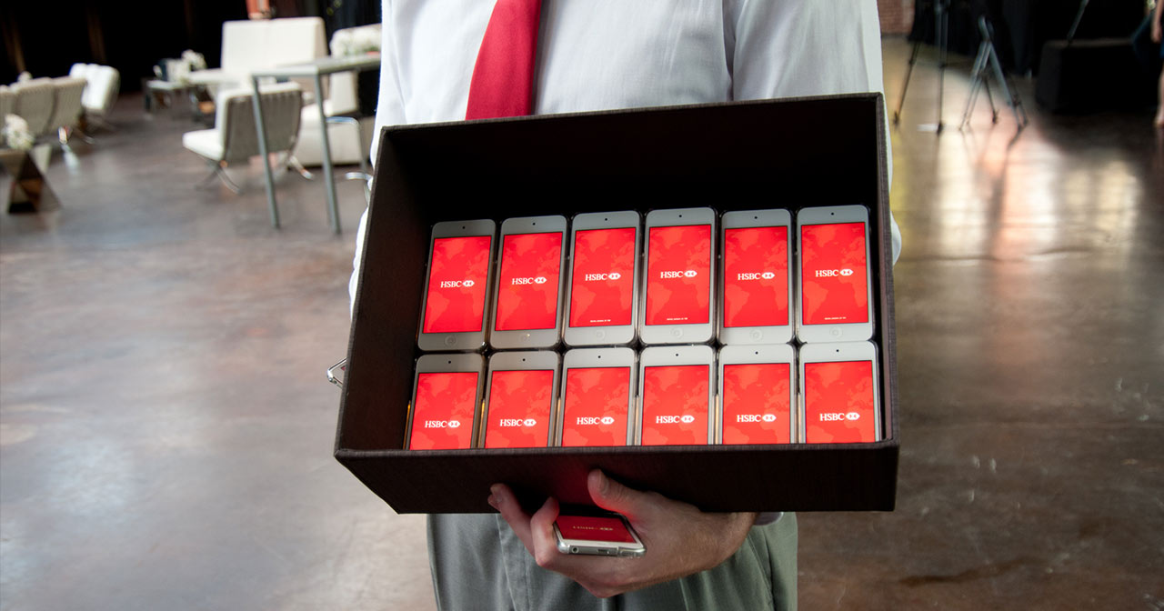 A person holds a box filled with iPods all displaying HSBC logo on the screens
