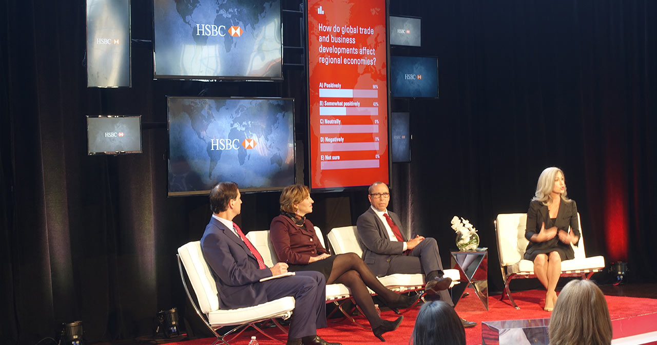 4 people sitting on stage talking to the audience. A screen behind them shows a live multiple choice question.