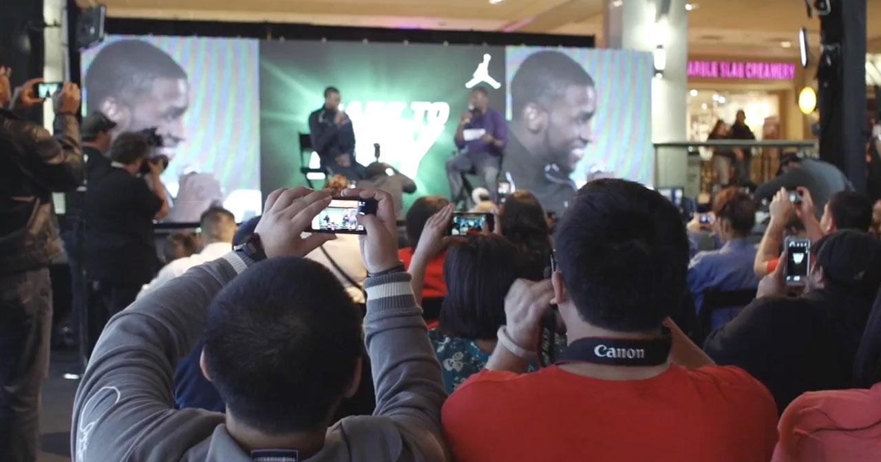 Crowd holding phones up to photograph or record NBA players being interviewed on stage.