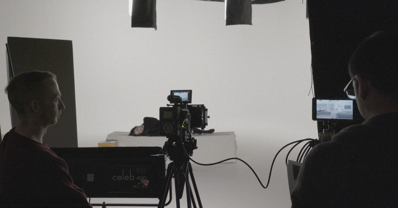 Behind the scenes photo taken from behind a video camera looking at an actress sleeping on a bed.