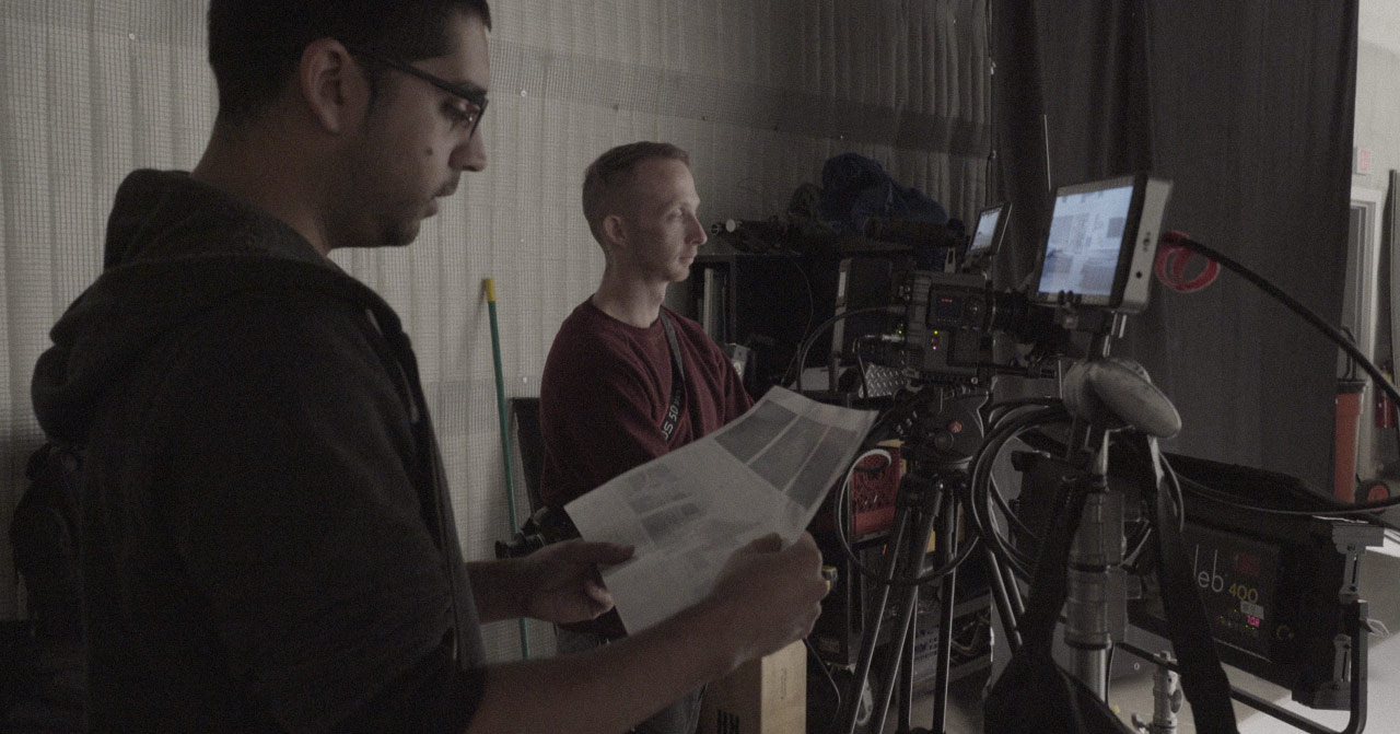 Two people standing behind cameras looking at a storyboard