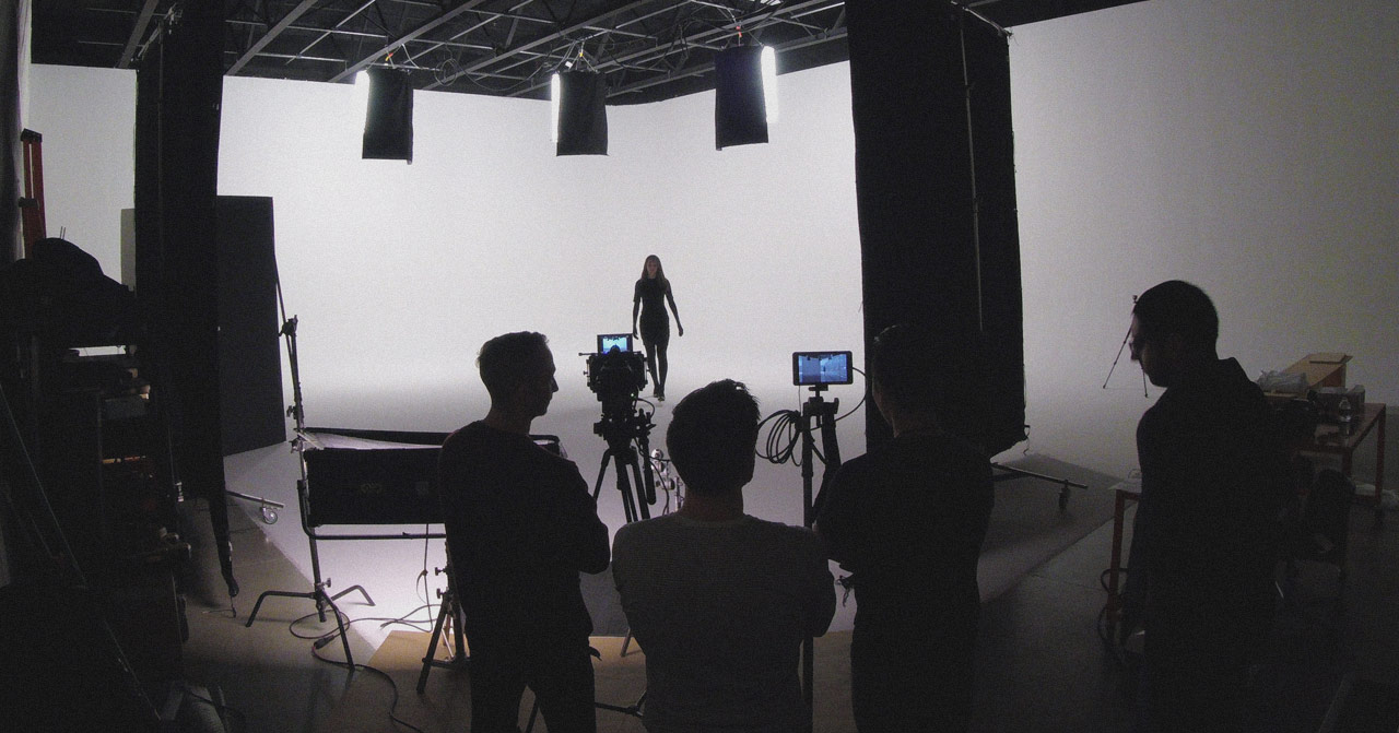 Four people behind cameras watching actress walk towards the camera.