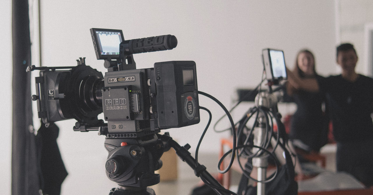 Shot of a video camera with two people blurred in the background.
