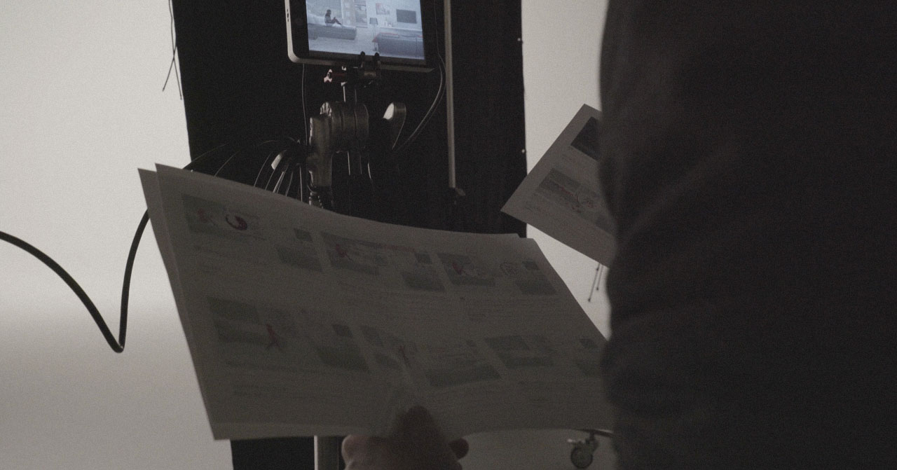 Close up of a person shuffling through pages of a storyboard with a screen in front of them.