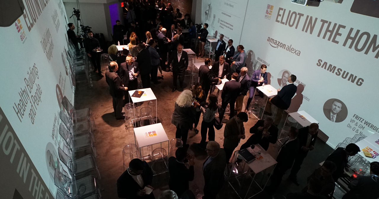 Overhead shot of room full of business people mingling with video projections on the walls.