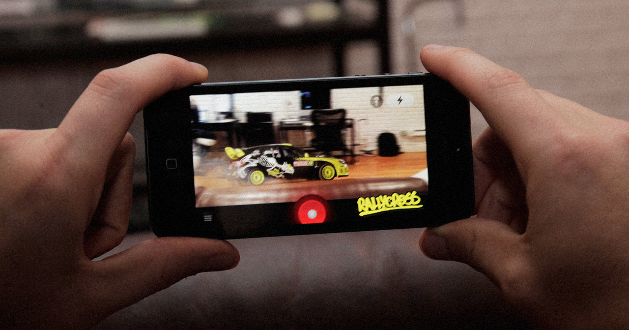 Close up of two hands holding a phone displaying a small car driving over a couch in augmented reality