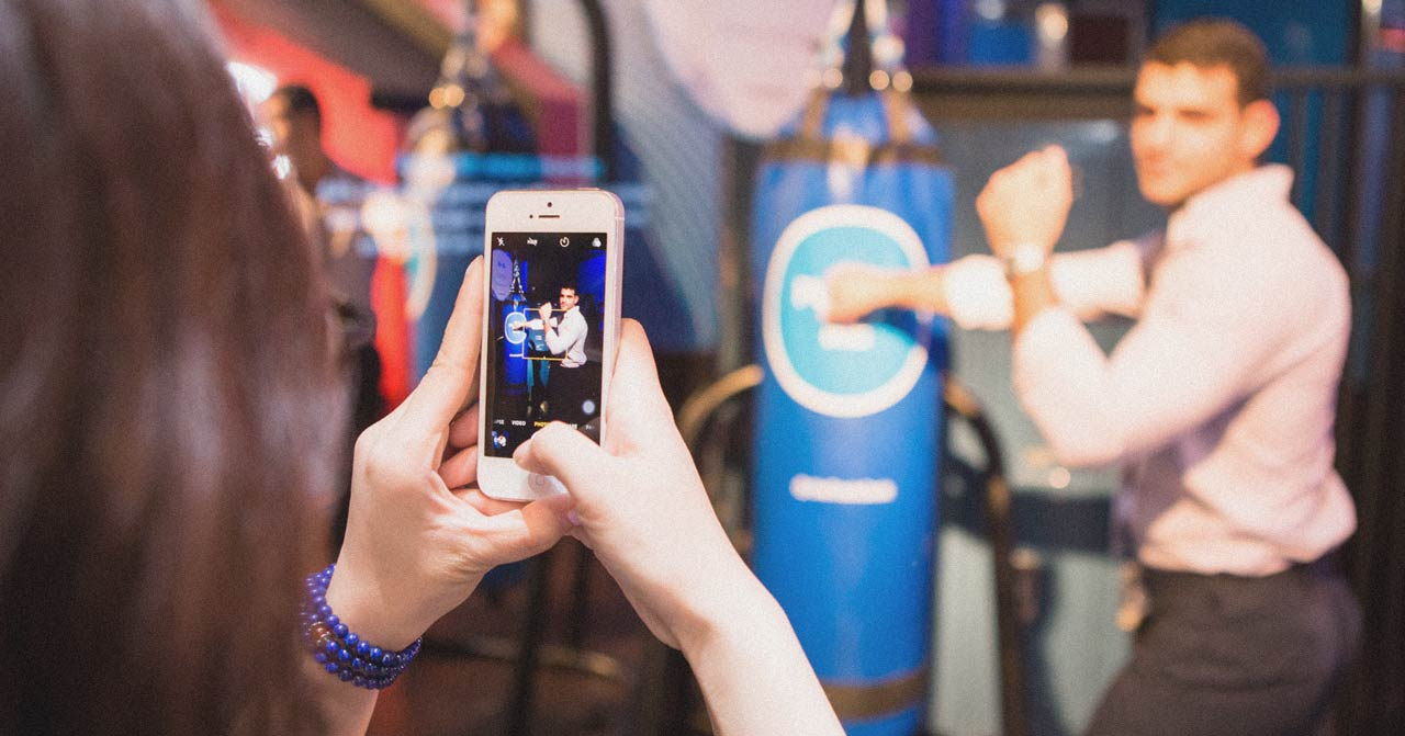 Woman photographs a man posing in front of a punching bag