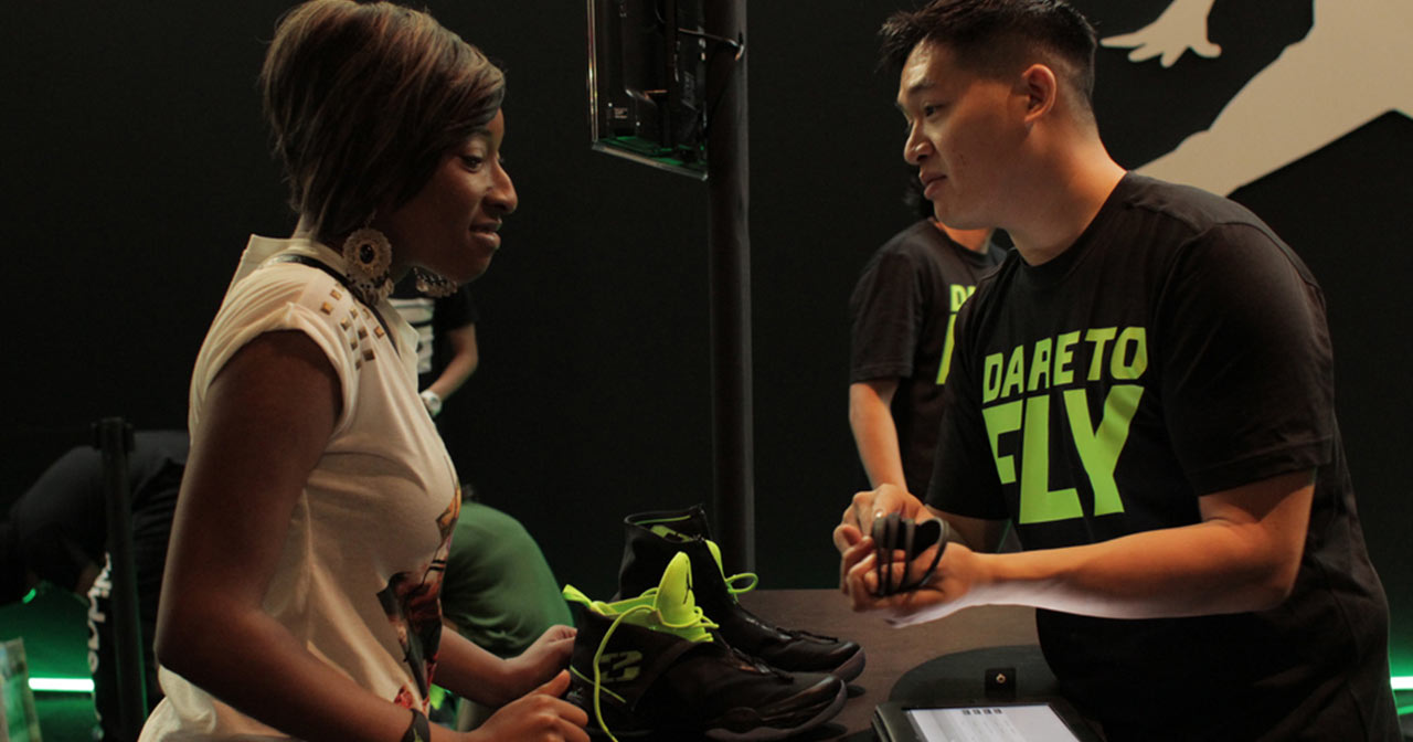A woman receives her AJXX8 sneakers from a Nike rep