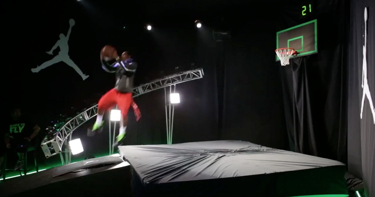 A young man jumping off a springboard in an attempt to dunk a basketball