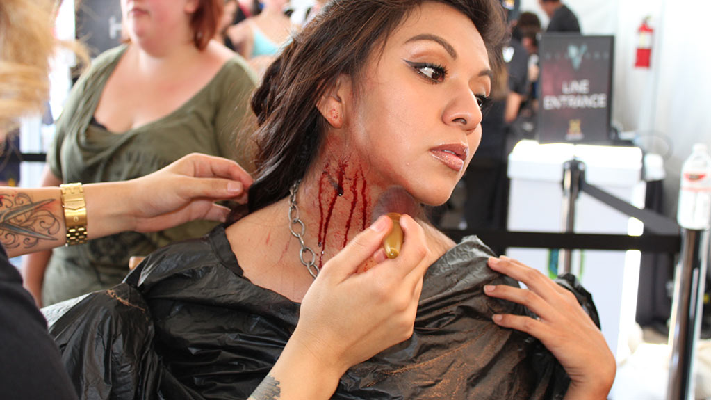 An woman is prepped at the make up station where she is getting blood and scars applied to her neck.