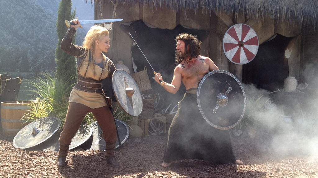 Two people dressed as vikings swordfight in front of a hut.