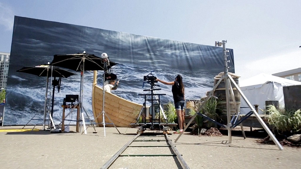 Camera on a track filming comic con attendee pretending to be a viking on a boat with a huge ocean backdrop